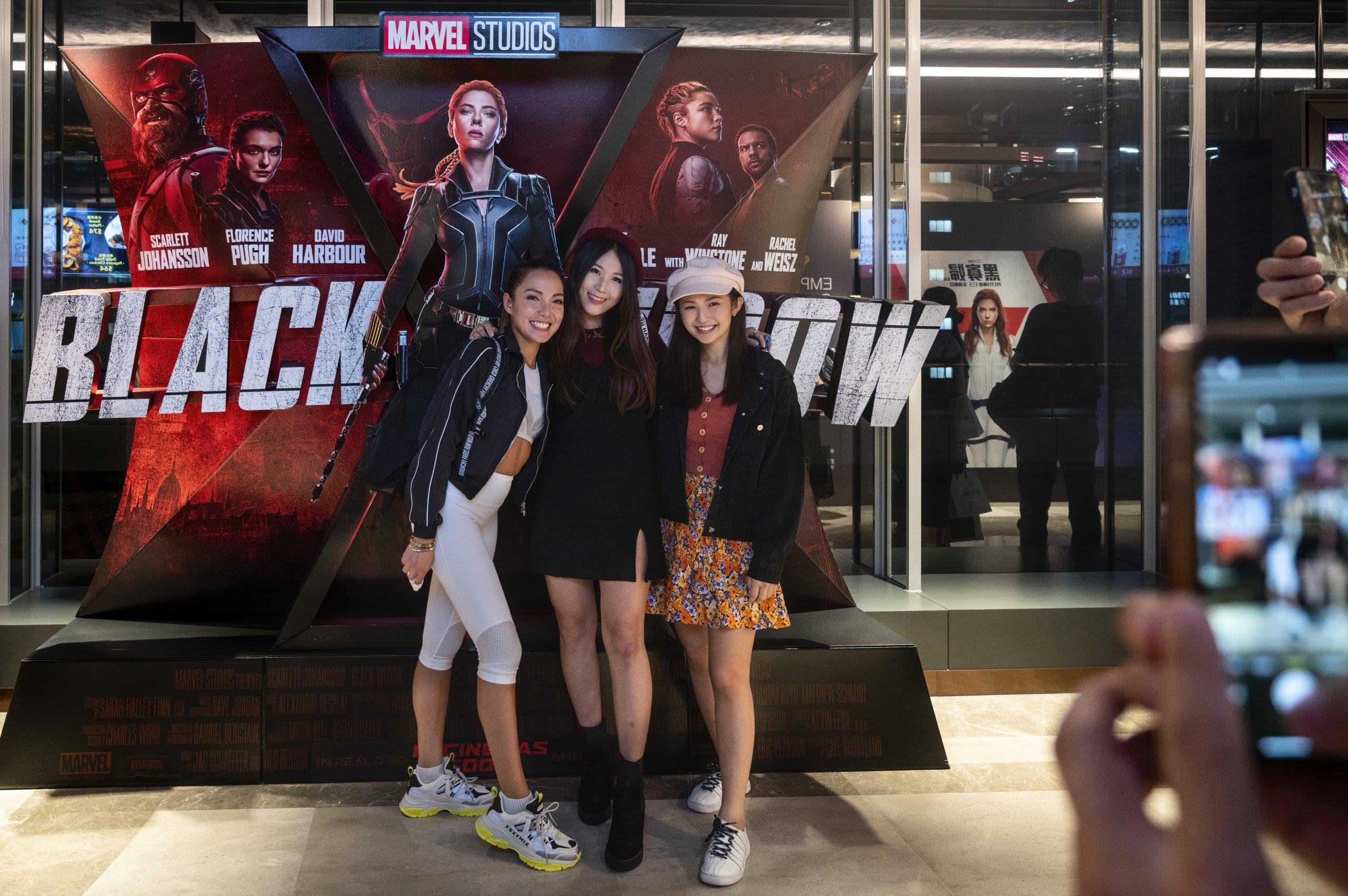 Spectators Pose In Front Of Disney's And Marvel Studios